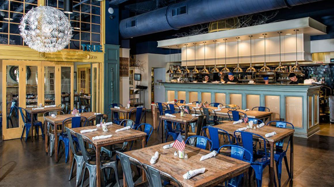 wooden tables and blue metal chairs in restaurant